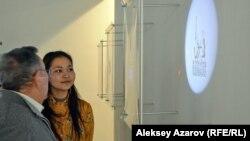 Шекер Шакир с посетителем-мужчиной перед одной из представленных ею инсталляций. Если на наклейку на пластиковой коробке светить фонариком, то на стену проецируется картинка.