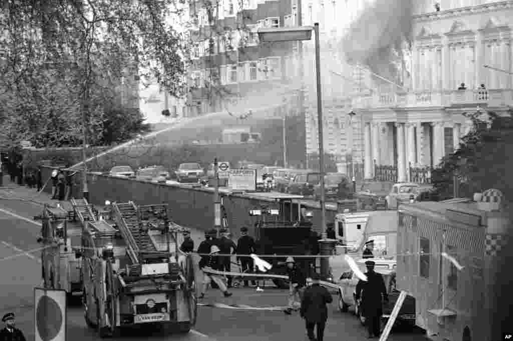 Flames and smoke billow from the embassy after explosions rocked the building. The rescue operation took 11 minutes. Five of the six hostage takers were killed after SAS commandos stormed the embassy.