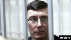 Former Interior Minister Yuriy Lutsenko looks out from the defendant's cage during a court session in Kyiv in February.