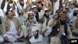 Supporters of the hard-line pro-Taliban Pakistani party Jamiat Ulema-e Islam (JUI) carry a portrait of slain Al-Qaeda leader Osama bin Laden at a rally in Quetta on May 2, 2013.