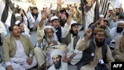 FILE: Pakistani supporters of hard-line pro-Taliban party Jamiat Ulema-e-Islam (JUI) carry a portrait of the slain Al-Qaeda leader Osama bin Laden during a protest in 2013.