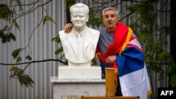 Человек позирует с бюстом Милошевича на могиле бывшего сербского лидера, 11 марта 2016 года.