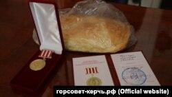 Хлеб и юбилейные медали, которые депутаты дарили керчанам, пережившим блокаду Ленинграда