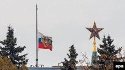 Российский государственный флаг рядом со зданием Кремля в Москве.