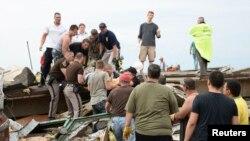 Спасатели вытаскивают из-под завалов одного из пострадавших. Город Мур, штат Оклахома, 20 мая 2013 года.