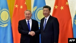 Kazakh President Nursultan Nazarbayev (L) and Chinese President Xi Jinping shake hands before their meeting at the Great Hall of the People, on the sidelines of the Belt and Road forum in Beijing on May 14.