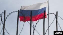 Флаг России за колючей проволокой.