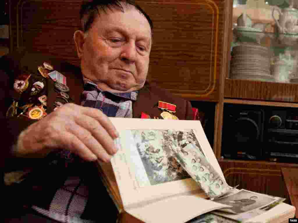 آلکسی ویتسن، زندانی پیشین سوبیبوردر حال بازشناسی ایوان دمیانیوک در میان تصاویر به جای مانده از اردوگاه سوبیبور