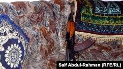 Ирак отбасының үйінде қабырғаға сүйеулі тұрған қару. (Көрнекі сурет)