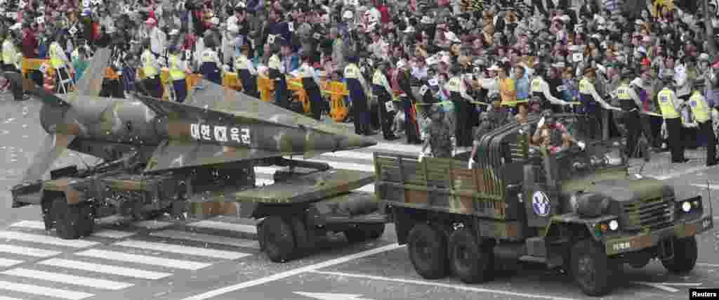 """1 қазанда Оңтүстік Корея алыс қашықтыққа ұшатын жаңа зымыранын көрсетті. Сеулде өткен әскери парадта 11 мыңға тарта әскери қызметкер, 120 ұшақ пен тікұшақ, 190 қару-жарақ пен әскери техника түрлері көрсетілді. Қару-жарақтардың арасында радиусы 1 мың километрге жететін жаңа """"Хенде-3"""" зымыраны бар. Суретте: Сеулдегі әскери парад. 1 қазан 2013 жыл."""