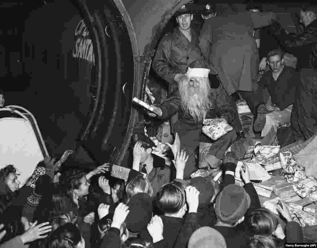 Young Berliners get a treat at Tempelhof Airport in Berlin on December 15, 1948: Christmas gifts from a flying Santa Claus, also known as Lieutenant John Konop of Astoria, New York. This was the first planeload from American donors to be distributed under the U.S. Air Force program known as Operation Santa Claus.