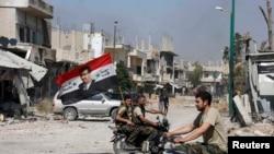Сторонники режима Башара Асада везут флаг Сирии по улицам Кусейра. 5 июня 2013 года.