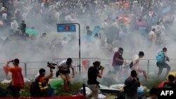 Полиция көзден жас ағызатын газ қолданғаннан кейін бас сауғалап бара жатқан шерушілер. Гонконг, 28 қыркүйек 2014 жыл.