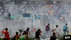 Protesters disperse after police fire tear gas near the Hong Kong government headquarters on September 28.