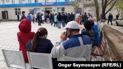 Люди в очереди у отделения почты для открытия счетов на получение государственного пособия во время режима ЧП, введенного из-за коронавируса. Кызылорда, 13 апреля 2020 года.