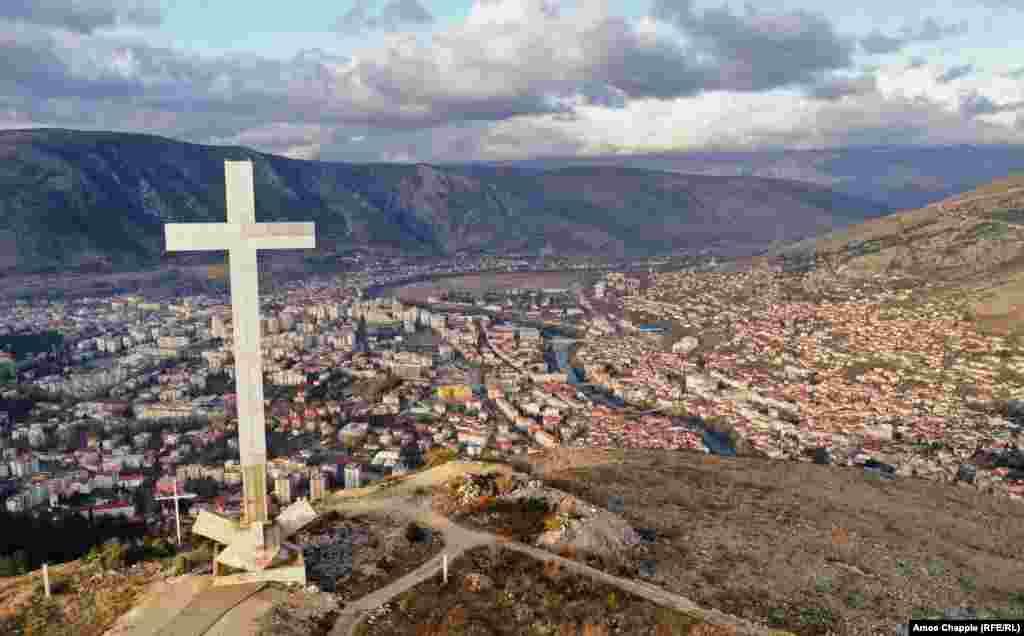 Поглед на Мостар во која доминира крст висок 33 метри. Од крајот на конфликтот во 1994 година, Мостар е поделен со Хрватите кои претежно живеат на западната страна на реката Неретва (лева страна на фотографијата) и Бошњаците на исток.