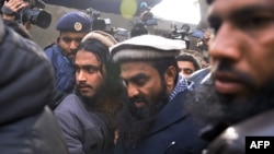 Pakistani security personnel escort Zakiur Rehman Lakhvi (center), the alleged mastermind of the 2008 Mumbai attacks, as he leaves a court in Islamabad in 2014.
