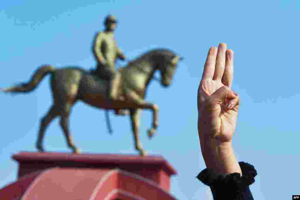 A protester holds up the three finger salute during a demonstration against the military coup at the monument of General Aung San (L), the late father of Suu Kyi in Naypyitaw on February 8, 2021 (Photo by STR / AFP)