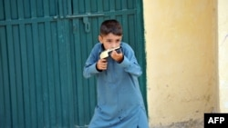 A boy holds a toy gun near the closed house of Rimsha, a Christian girl who has been arrested on blasphemy charges, in a slum area of Islamabad.