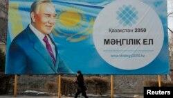 Женщина проходит мимо билборда с изображением президента Нурсултана Назарбаева. Алматы,16 февраля 2015 года.