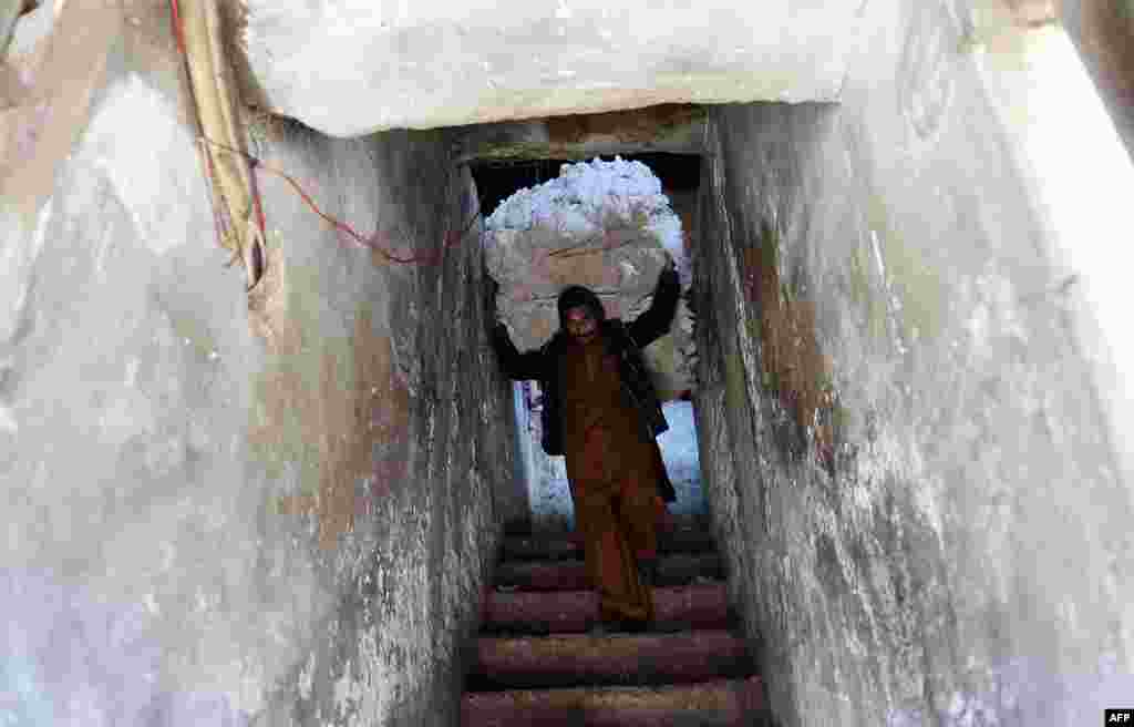 A Pakistani labourer shifts a bundle of cotton from a store onto his cart at a market in Rawalpindi on March 10. (AFP/Farooq Naeem)