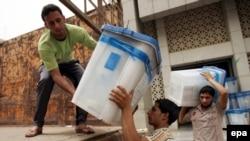 عمال ينقلون صناديق إقتراع من مركز إنتخابي ببغداد في 14 آيار 2010