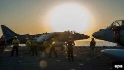 АҚШнинг AV-8B Harrier ҳарбий самолёти кема бортидан ҳавога кўтарилишга ҳозирлик кўрмоқда.