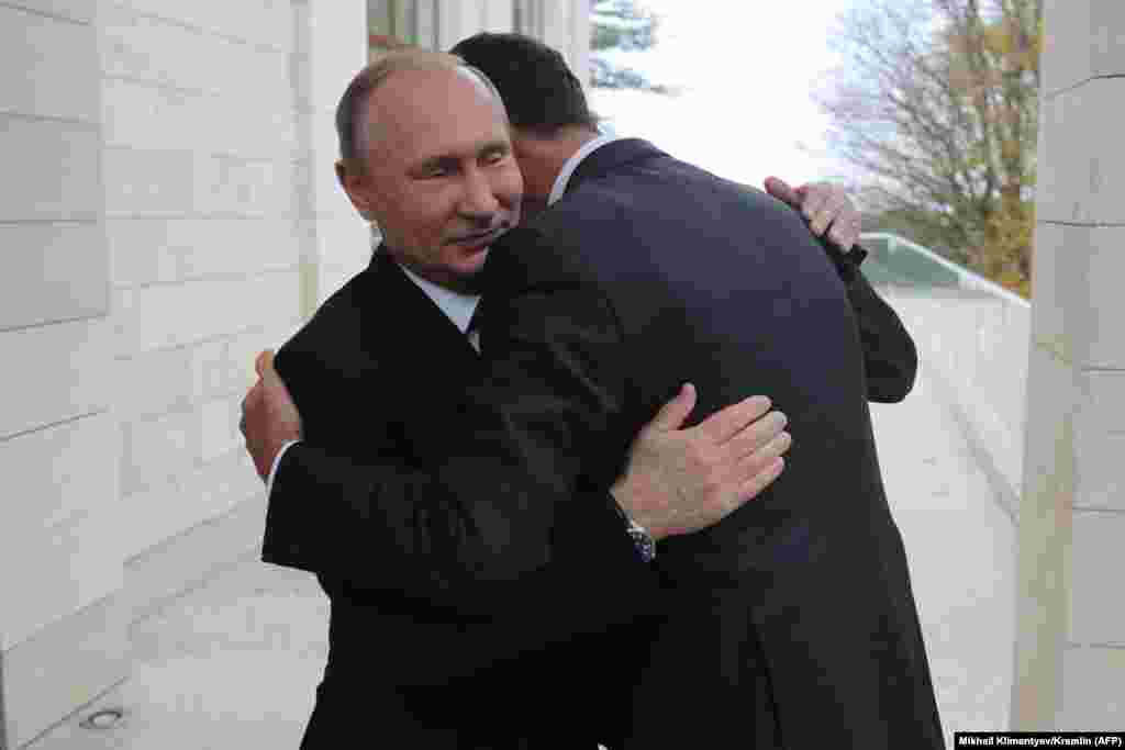 Russian President Vladimir Putin (left) and his ally, Syrian President Bashar al-Assad, embrace during a meeting in Sochi on November 20. (AFP/Mikhail Klimentyev)