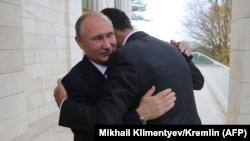 Президент России Владимир Путин (слева) обнимает своего сирийского коллегу Башара Асада во время встречи в городе Сочи. 20 ноября 2017 года.