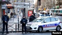 Белгісіз ер адам шабуылдамақ болған полиция бөлімшесі алдында тұрған құқық қызметкерлері. Париж, 7 қаңтар 2016 жыл.