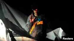 Dzhokhar Tsarnaev is shown before his arrest with a sniper's laser sight trained on his head as he surrenders to authorities on April 19, 2013, after a massive manhunt.