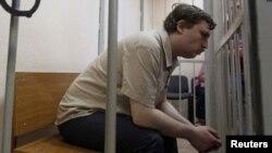 Михаил Косенко «Болотное иши» боюнча сотто баш коргоо чарасын кароо учурунда. 2013-жылдын майы. Кийин Михаил психиатриялык мажбур дарылоого жөнөтүлгөн. Сүрөт: Reuters.