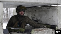 A Ukrainian serviceman guards a checkpoint near the town of Svitlodarsk.