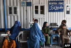 Afghan refugees wait at the UNHCR registration center in the Pakistani city of Peshawar in June.