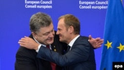 Ukrainian President Petro Poroshenko (left) and EU Council President Donald Tusk hug each at an EU summit in Brussels on February 12.
