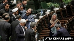 "An Iranian lawmaker uses a phone to take a ""selfie"" picture as EU foreign-policy chief Federica Mogherini walks by in parliament in Tehran on August 5."