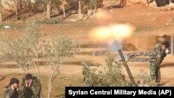 تصویر منتشر شده توسط تلویزیون مرکزی ارتش سوریه، نیروهای دولتی این کشور را در حال شلیک خمپاره به سوی مواضع معارضان بشار اسد