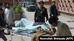 Afghan volunteers carry an injured man on a stretcher to a hospital following a bomb blast in Jalalabad on March 19.