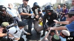 Israeli riot police detain a protester after Israeli students rallied against a plan to continue the construction freeze in the West Bank.