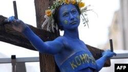 Девушка символизирует украинскую Конституцию. Снимок перформанса гражданских активистов у здания Конституционного суда сделан год назад: тогдашняя оппозиция считала, что власть Януковича распяла Основной закон страны