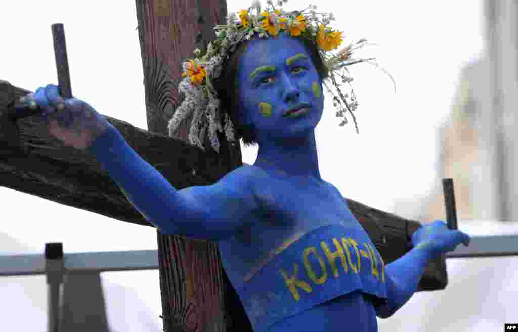 """A woman symbolizing the Ukrainian Constitution is """"crucified"""" during a performance called by Guy Fawkes activists in front of the Constitutional Court building in Kyiv. The activists are calling on Ukrainians to take action to defend the constitution. (AFP)"""