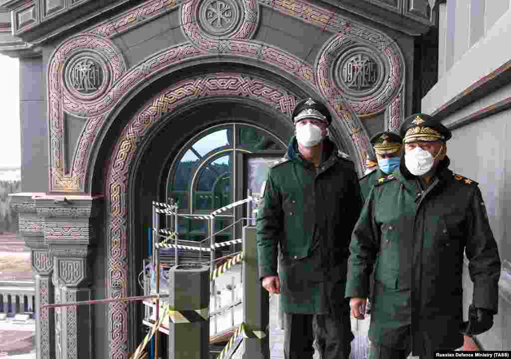 Russian Defense Minister Sergei Shoigu (right) visits the cathedral on April 22. The decorative reliefs in the background mark the start and finish of what Russians call the Great Patriotic War, which began for Soviets in 1941 with the Nazi invasion of the U.S.S.R. and ended with Germany's defeat in Europe in 1945.