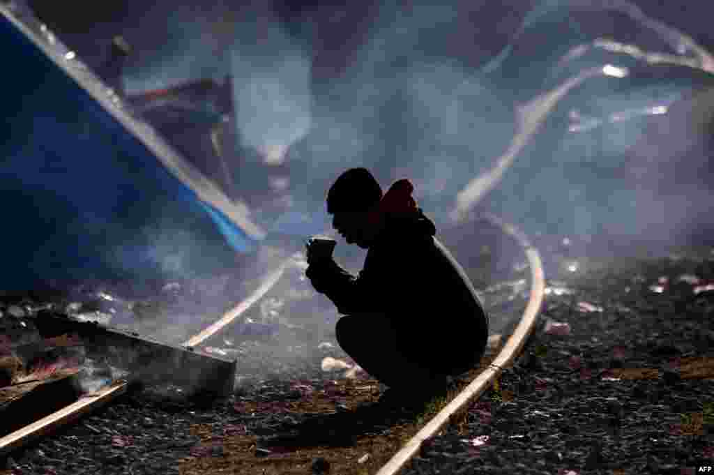 Чалавек сядзіць на чыгуначнай каляіне на грэцка-македонскай мяжы, дзе сабралася шмат мігрантаў і ўцекачоў. (AFP/Sakis Mitrolidis)