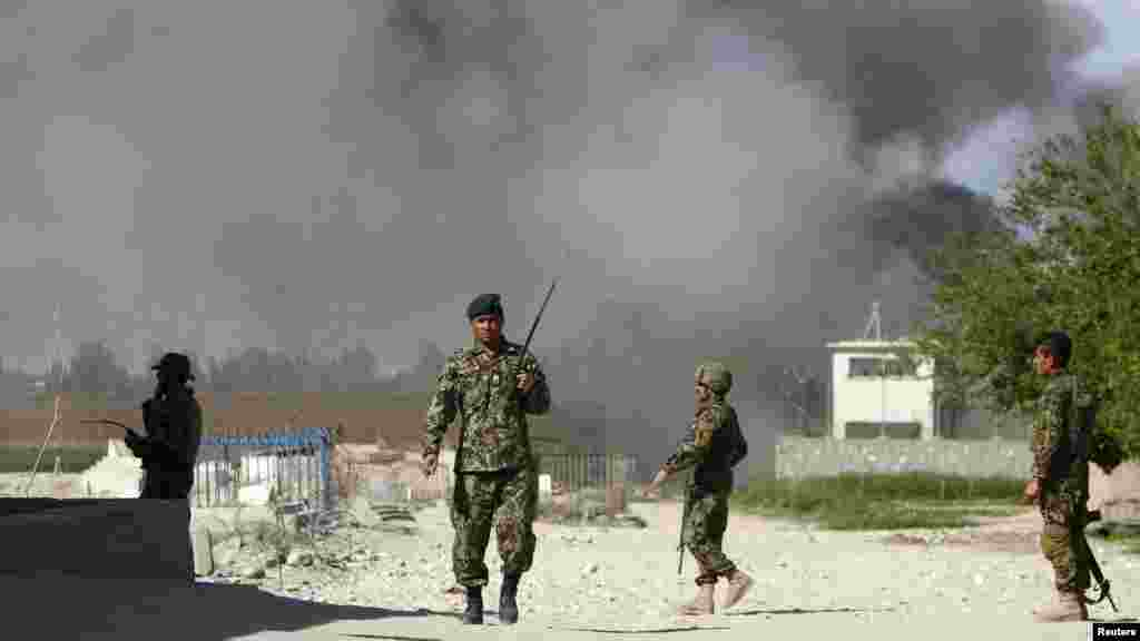 Soldiers from the Afghan National Army keep watch near a Provincial Reconstruction Team as smoke rises from the site of an attack in Jalalabad Province on April 15. (REUTERS/Parwiz)