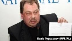 """Михаил Сизов """"министрліктің хаты"""" деген құжатты көрсетіп отыр. Алматы, 22 қаңтар 2013 жыл."""