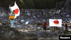 Члены японской националистической организации водружают флаги Японии на островах Сенкаку, август 2012 года