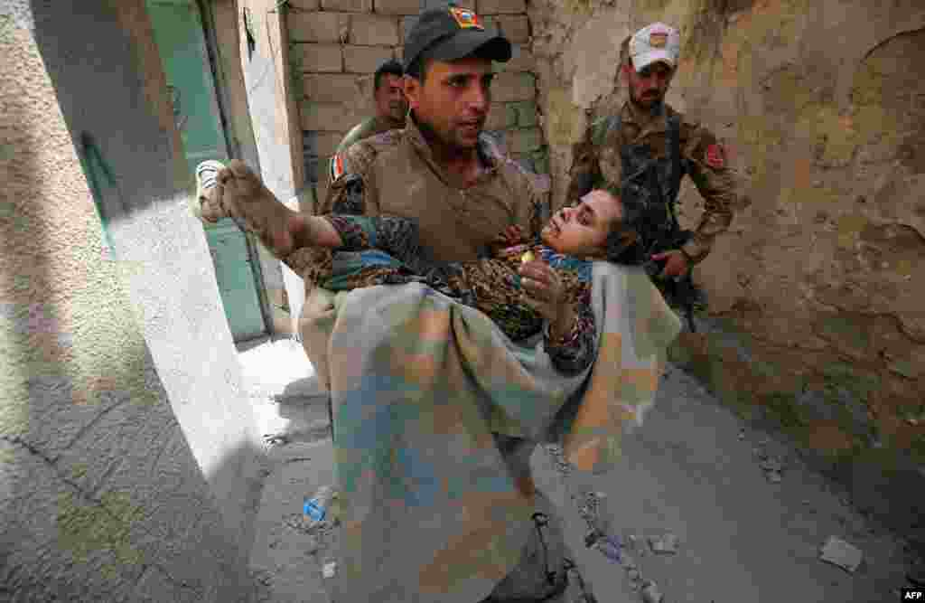 A member of the Iraqi Counterterrorism Service carries a wounded girl in the Old City of Mosul on July 3 during an ongoing offensive to retake the city from Islamic State extremists. Iraqi forces have been closing in on the Old City in western Mosul for months, but the terrain, combined with a large civilian population, has made for an extremely difficult fight. (AFP/Ahmad al-Rubaye)