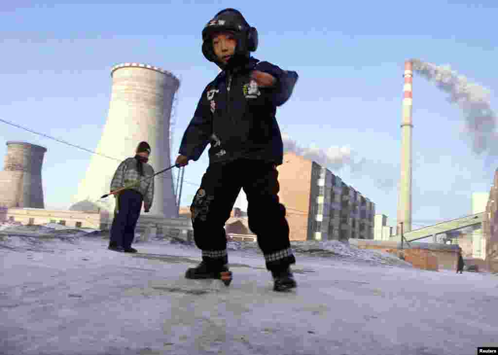Boys spin tops in front of a coal-powered electricity plant in Xilinhot, Inner Mongolia, China.