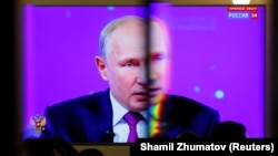 Russian President Vladimir Putin is seen on a screen through a glass door at a press centre during an annual nationwide televised phone-in show in Moscow, Russia June 20, 2019. REUTERS/Shamil Zhumatov - RC14F5EBD700