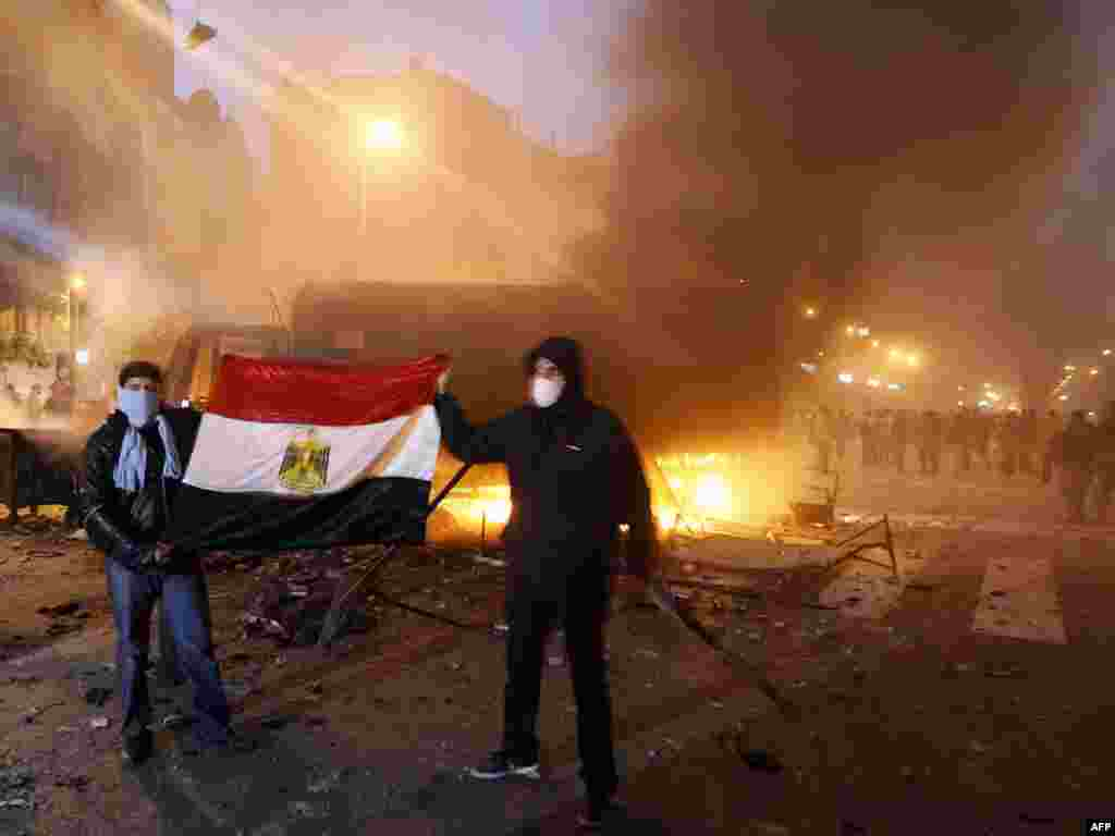 Masked Egyptian demonstrators hold the national flag as they stand next to a burning police vehicle in Cairo.